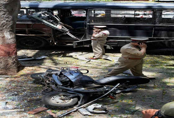 Police personnel inspect the site of the blast near the BJP office at Malleswaram in Bengaluru