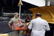 A Police man helps passenger to board his taxi as the political parties called strike today to protest against the state government
