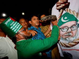 A Bangladeshi man throws a shoe at a Motiur Rahman Nizami poster to celebrate the execution of the Jamaat-e-Islami party's senior leader outside Dhaka's central jail, Bangladesh