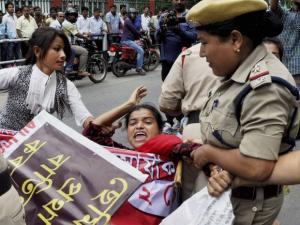 Security personnel drag away activists of All India Democratic Students Organisation