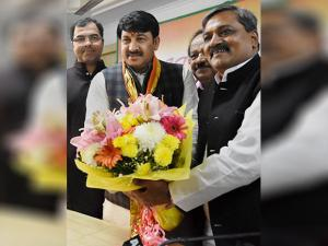 New BJP Delhi unit President Manoj Tiwari is greeted by his predecessor Satish Upadhyay after taking charge at the party office