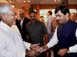 Bihar Chief Minister Nitish Kumar greets senior BJP leader Shahnawaz Hussain