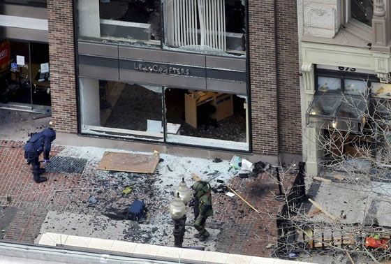 One of the blast sites on Boylston Street near the finish line of the 2013 Boston Marathon is investigated by two people in protective suits