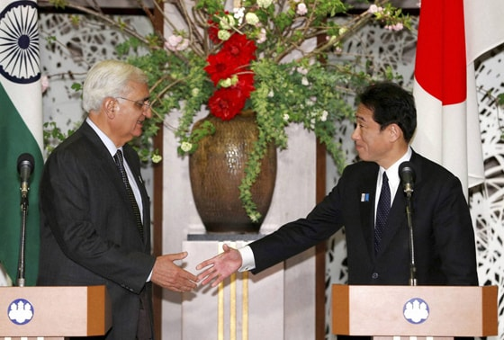 Indian Foreign Minister Salman Khurshid, left, shakes hands with his Japanese counterpart Fumio Kishida