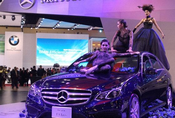 Thai models pose on a Mercedes-Benz E-class