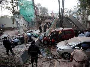 Police and rescue officials clear debris from the site of a collapsed building which killed a cab driver in Mumbai