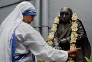 A Nun of the Missionaries of Charity garlands a statue of Mother Teresa
