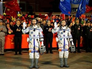 Chinese astronauts Jing Haipeng, right, and Chen Dong, left, wave farewell to the crowd before getting on Shenzhou 11 spacecraft