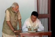 President of China Xi Jinping signing visitors' book as Prime Minister Narendra Modi look on at Gandhi Ashram