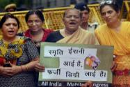 Congress women's wing activists hold placard during their protest against Union HRD Minister Smriti Irani