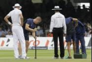 England's Stuart Broad watches as ground staff work on the pitch
