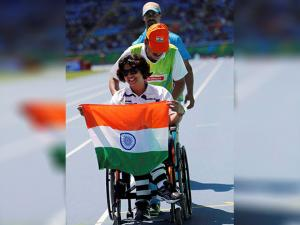 Deepa Malik holds her nation's flag after winning the silver medal in the women's shot put