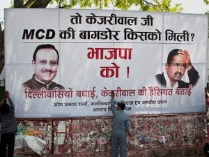 Workers put up a hoarding outside Delhi BJP headquarters in New Delhi