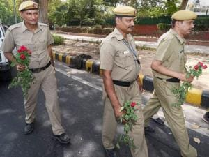 Delhi police carrying flowers for BJP MP Vijay Goel (unseen) as he voilated odd-even rule as a mark of protest, in New Delhi