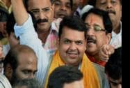 Devendra Fadnavis (C) flashes victory sign after he was announced as BJP legislative party leader in Mumbai