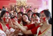 Women participate in Sindur Khela (playing with vermilion powder) at a community puja pandal
