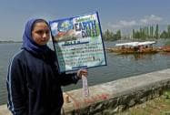 A school girl hold placards on the banks of Dal Lake to mark World Earth Day in Srinagar