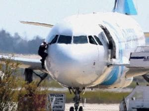 A man, leaves the hijacked aircraft of Egyptair from the pilot's window after landing at Larnaca airport