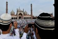 Two Muslim boys clicking pictures of others as they celebrate on the occasion of 'Eid-Ul-Fitr' at Jama Masjid
