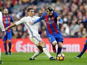 Lionel Messi escapes Real Madrid's Cristiano Ronaldo during the Spanish La Liga soccer