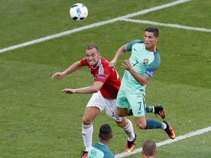 Portugal's Cristiano Ronaldo, right, looks the ball before scoring his side's 3rd goal  during the Euro 2016