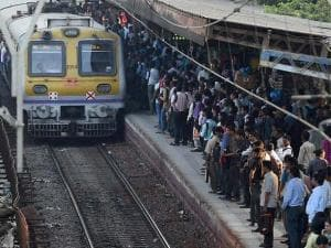 commuters wait to board trains at a railway station on the eve of the railway budget in mumbai