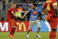 Belgium's Kevin De Bruyne holds on to a spectator who ran on to the pitch during the World Cup