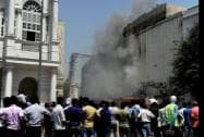 People watch as smoke billows out after a massive fire broke out at Rama Building in Connaught Place