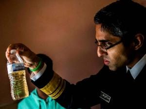 Surgeon General Vivek Murthy inspects a bottle of water which contains water from Flint resident Tia Simpson's tap at her home