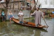 People move towards safer places on a boat at flood-hit Rainawari area of Srinagar