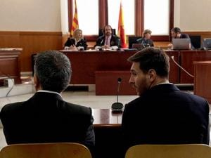 Barcelona's Lionel Messi, right, and his father Jorge Horacio Messi sit in court in Barcelona, Spain