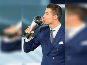 Cristiano Ronaldo, who plays for Real Madrid, kisses the trophy