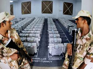 Security officers guard sealed electronic voting machines (EVMs) at GCT College in Coimbatore after elections