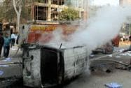 A fireman dousing a burning vehicle set ablaze by irate worker
