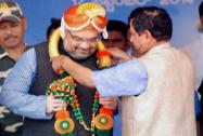 BJP National President Amit Shah is garlanded by Karnataka BJP chief Prahlad Joshi