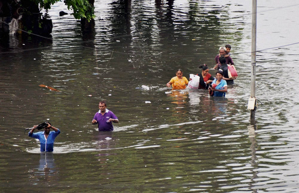 Commuters, wade, through, flooded, water, heavy rain, Ahmedabad