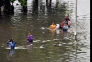 Commuters wade through flooded water during heavy rain in Ahmedabad