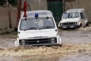 Police vehicles moves through a flooded road at Mehjoor Nagar in Srinagar