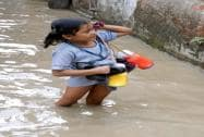 A little school girl wades through road flooded by river Ganga near Kalighat Kali temple
