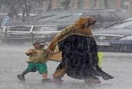 A women crosses the road with her child in heavy rains in Kolkata