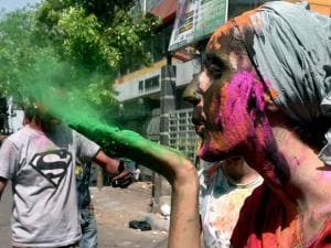 A Foreign tourist sprays colour while celebrating Holi in Culcatta