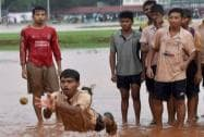 Boys play in the rain water at Azad Maidan in Mumbai
