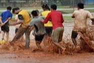 Boys play soccer in the rain at Azad Maidan in Mumbai