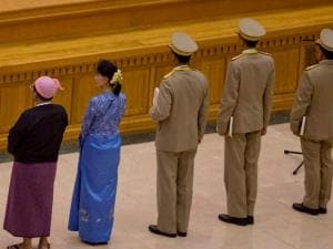 National League for Democracy party leader Aung San Suu Kyi, second left, stands before taking oaths with other lawmakers as a cabinet minister at parliament in Naypyitaw