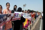 Girl students make a human chain during a protest over violence against women