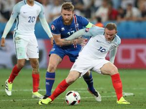 Iceland's Aron Gunnarsson, left, challenges England's Wayne Rooney during the Euro 2016