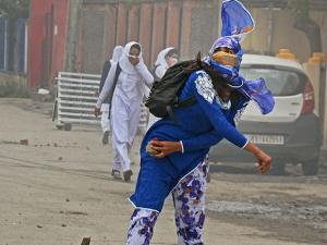 A girl student pelts a stone at security personnel