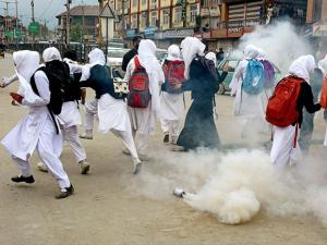 Girl students run for cover as police burst tear gas shells during clashes