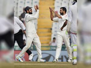 Indian captain Virat Kohli celebrates with Mohammed Shami the wicket of England batsman Adil Rashid