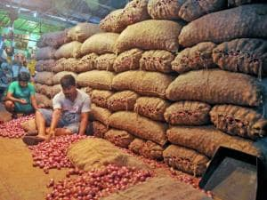 Labourers sorting onions at a storehouse of a wholesale market